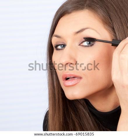 portrait of a beautiful young woman applying mascara - stock photo