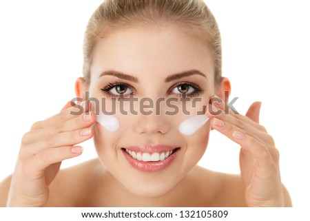 Portrait of a beautiful young woman applying moisturizer cream on face over white background - stock photo
