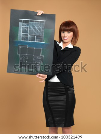 portrait of a beautiful, young woman architect, showing a blueprint, on beige background - stock photo