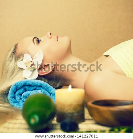 Portrait of a beautiful young woman at a spa salon. Perfect skin and long blond hair with white orchid. Skincare and haircare. Young skin. Close up. Copy-space. Indoor shot - stock photo