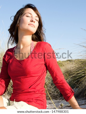 Portrait of a beautiful young woman breathing fresh air while sitting on a beach sand dunes with grass, leaning her head back and enjoying the breeze on vacation.