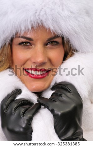 portrait of a beautiful young woman dressed in white fur coat and hat - stock photo