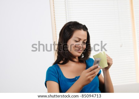Portrait  of a beautiful young woman  drinking coffee and using  a mobile phone. - stock photo