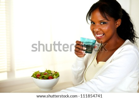Portrait of a beautiful young woman drinking water and eating a healthy green salad while looking at you. With copyspace. - stock photo
