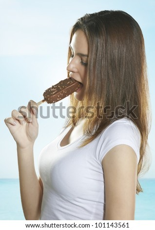 Portrait of a beautiful young woman eating a delicious ice cream - stock photo