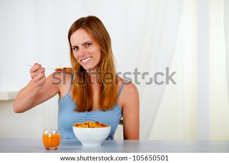 Portrait of a beautiful young woman eating cereals and strawberry for breakfast at home - stock photo