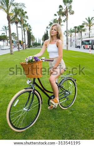 Portrait of a beautiful young woman enjoying a weekend rest after ride in the park on her classic bicycle, attractive female hipster in stylish clothes posing outdoors for the camera with retro bike  - stock photo