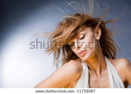 Portrait of a beautiful young woman enjoying the wind - stock photo
