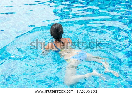 Portrait of a beautiful young woman floating in the pool. Concept photo healthy lifestyle - stock photo