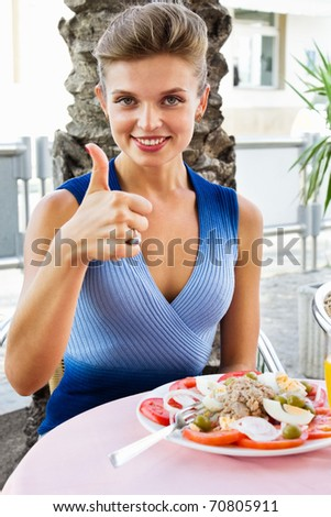 Portrait of a beautiful young woman gesturing ok sign at a restaurant - Outdoor