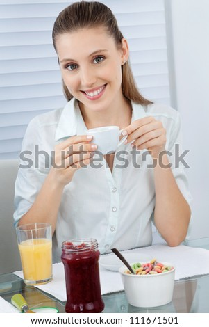 Portrait of a beautiful young woman having tea with juice, jam jar and cereal bowl at table