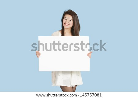 Portrait of a beautiful young woman holding blank cardboard over blue background