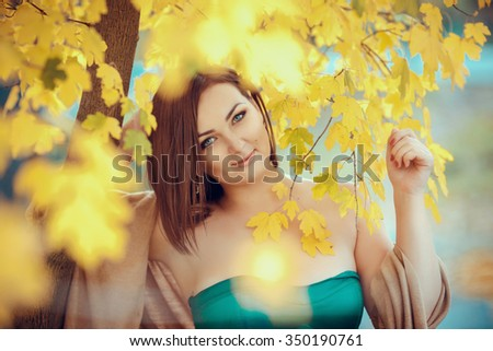 portrait of a beautiful young woman in a autumn park. pictures in warm colors. Model plus