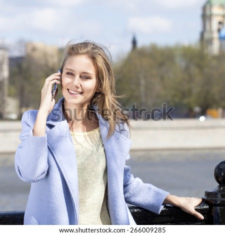 Portrait of a beautiful young woman in a blue coat - stock photo