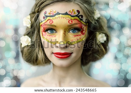 Portrait of a beautiful young woman in a carnival mask - stock photo