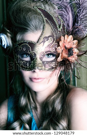 Portrait of a beautiful young woman in a carnival mask. Vintage style. - stock photo