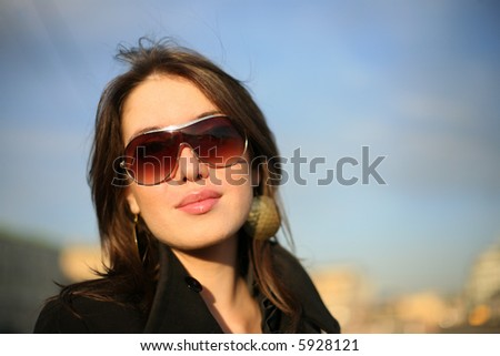 Portrait of a beautiful young woman in a city. Shallow DOF. - stock photo