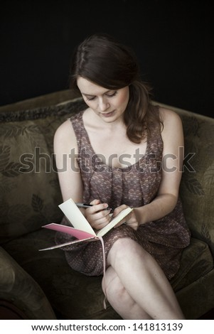 Portrait of a beautiful young woman in a dress writing in her journal - stock photo
