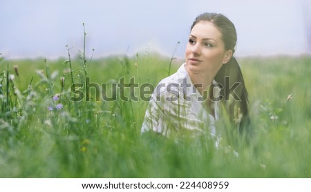 Portrait of a beautiful young woman in a grass, outdoors. Close up of a female in a nature. Healthy enjoy - stock photo