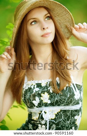 portrait of a beautiful young woman in a hat  with a green background - stock photo