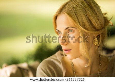 portrait of a beautiful young woman in a spring park. pictures in warm colors