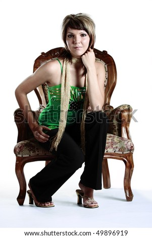 Portrait of a beautiful young woman in a studio with an isolated white background, sitting on a old fashioned wooden chair. - stock photo