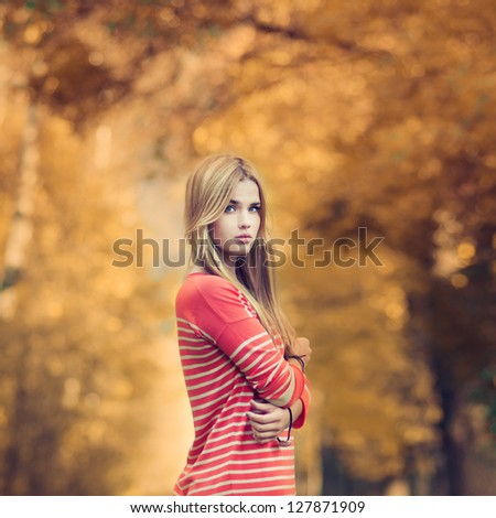 portrait of a beautiful young woman in a summer park. pictures in warm colors - stock photo