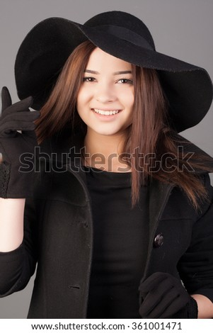 Portrait of a beautiful young woman in black hat, gloves and dress. Elegant girl concept. Lady with long hair.