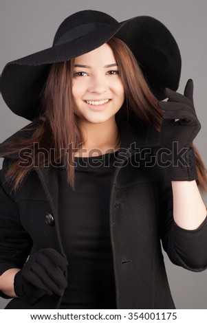 Portrait of a beautiful young woman in black hat, gloves and dress. Happy and elegant girl concept. Lady with long hair.