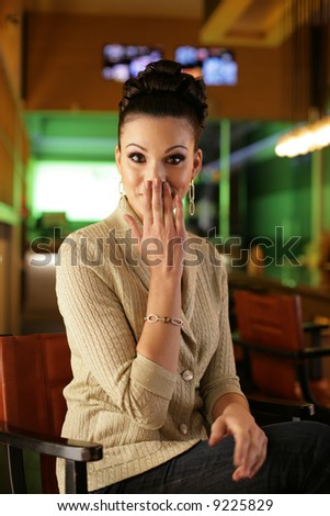 Portrait of a beautiful young woman in colorful office interior. Shallow DOF, focus on eyes. - stock photo