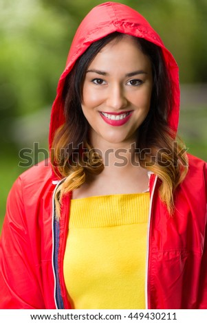 Portrait of a beautiful young woman in hooded red raincoat looking at camera and smiling while walking in the park on a rainy day.