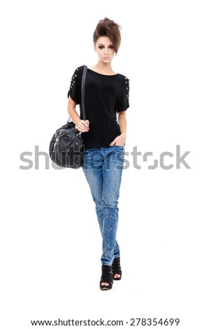 Portrait of a beautiful young woman in jeans with bag posing - stock photo