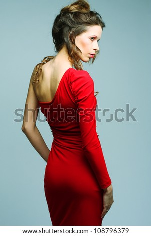 Portrait of a beautiful young woman in red dress. - stock photo
