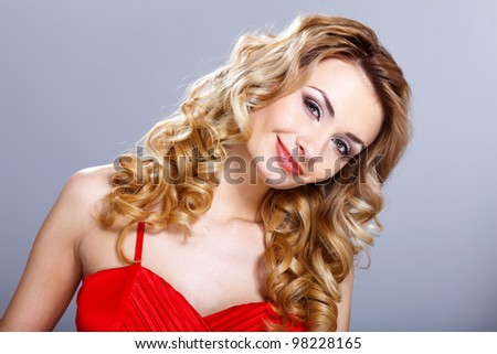 Portrait of a beautiful  young woman in red dress with curly hair - stock photo