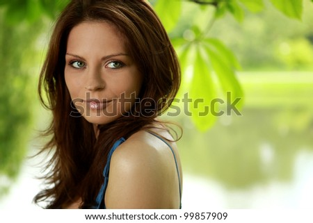 Portrait of a beautiful young woman in summer park - stock photo