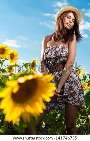 Portrait of a beautiful young woman in sunflower field - stock photo