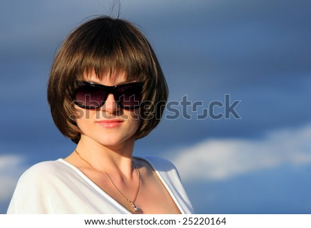 Portrait of a beautiful young woman in sunglasses with blue cloudy sky behind her.