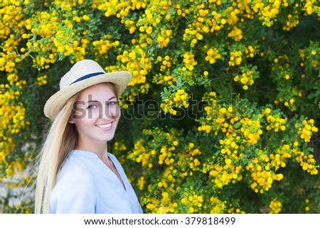 Portrait of a beautiful young woman in the hat with mimosa flowers background - stock photo