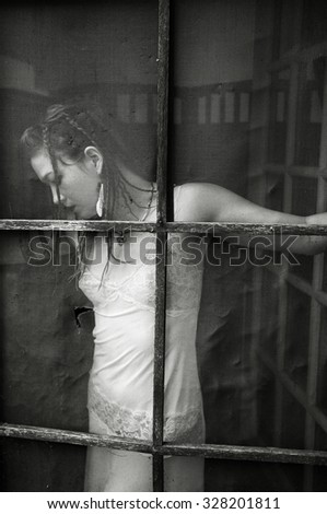 Portrait of a beautiful young woman in white negligee and braided hair shot through old screen door. in - stock photo