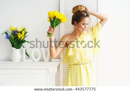 Portrait of a beautiful young woman in yellow dress with spring flowers and white decoration letters - stock photo