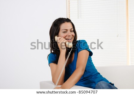 Portrait  of a beautiful young woman laughing and talking on the  phone.