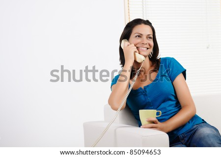 Portrait  of a beautiful young woman  laughing, talking on the phone and holding a cup. - stock photo