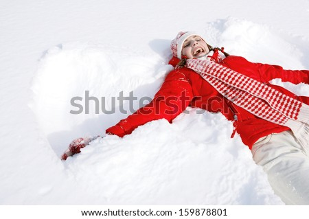 Portrait of a beautiful young woman laying down on a frozen snow lake moving her arms and legs up and down creating a snow angel figure, playing games during a sunny winter  vacation. - stock photo