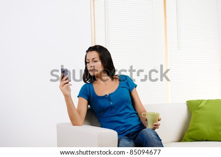 Portrait  of a beautiful young woman looking at mobile phone display. - stock photo