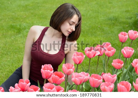 Portrait of a beautiful young woman looking at pink tulip garden - stock photo