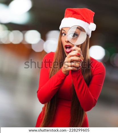 portrait of a beautiful young woman looking through the magnifying glass at Christmas - stock photo