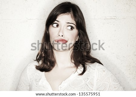 Portrait of a beautiful young woman looking to her left with a frowny expression, looking very worried and pessimistic about some matter. - stock photo