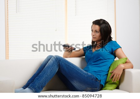 Portrait  of a beautiful young woman lying on a couch and watching TV. - stock photo