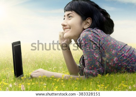 Portrait of a beautiful young woman lying on green grass with laptop computer and looking at sky - stock photo