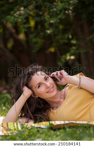 Portrait of a beautiful young woman lying on the grass at park and talking on phone - stock photo